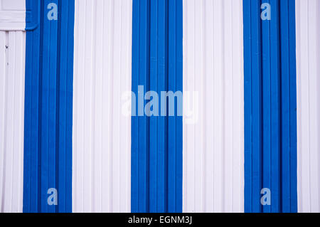 A corrugated metal door painted in Mediterranean colors - Stock Photo
