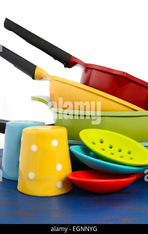 Bright colorful modern kitchen pot and pans in red, yellow, blue and green theme with spoons and salt and pepper - Stock Photo