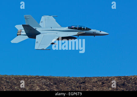 Close Up Topside View Of A US Navy F/A-18F Super Hornet Jet Fighter Flying Along The Rim Of A Desert Canyon. - Stock Photo