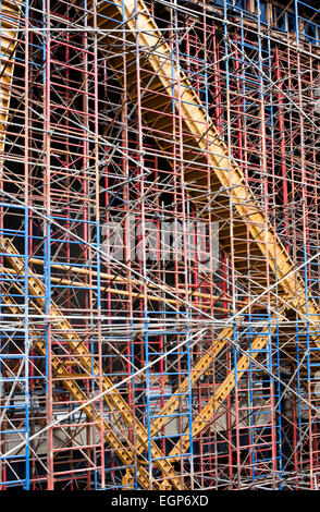 Colorful scaffolding and reinforcement at a construction site - Stock Photo