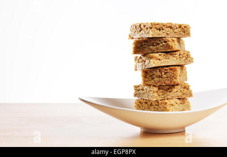 Gluten free home made flapjack served on a curved dish - Stock Photo