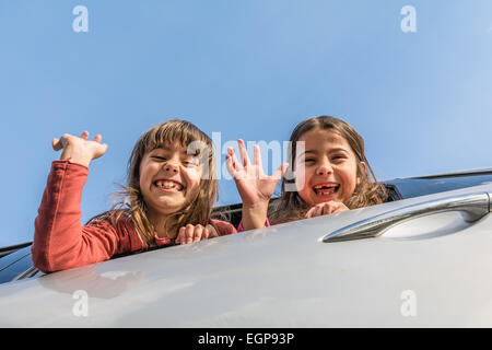 Two sisters going on a trip and waving from the car - Stock Photo