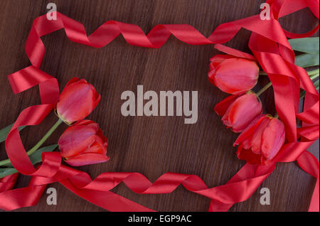 tulip on wooden background with red ribbon - Stock Photo