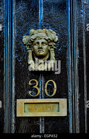 Georgian style brass door knocker depicting human head with letter box on black painted door, Londonderry, Derry, - Stock Photo