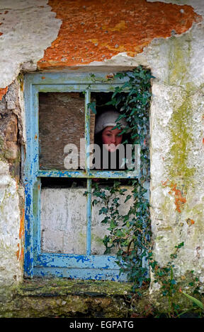 Young girl peeping  mysteriously out of the dirty broken window in an old abandoned house in Co. Cork Ireland - Stock Photo