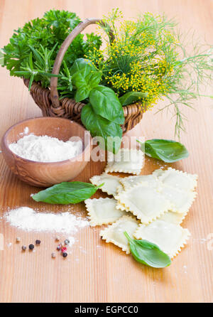 Homemade pasta ravioli with fresh basil, on wooden background - Stock Photo