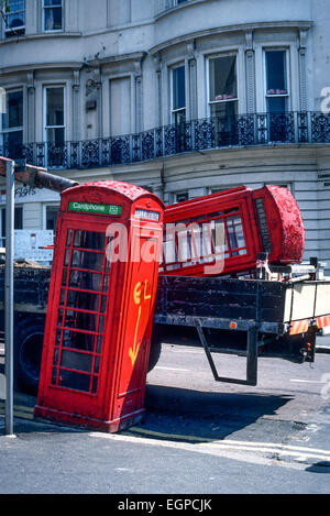 Two common red telephone boxes being removed from a street in Brighton, East Sussex, after decommissioning. - Stock Photo