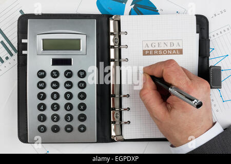 Diary, calculator,hand and pen  on a background of diagrams and graphs - Stock Photo
