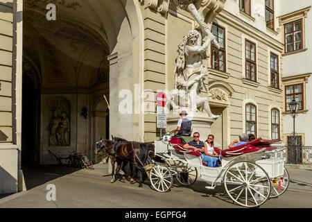 Horse carriage with tourists riding through a passage in Hofburg Palace, Vienna, Austria - Stock Photo