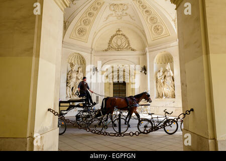 Horse carriage riding through a passage in Hofburg Palace, Vienna, Austria - Stock Photo