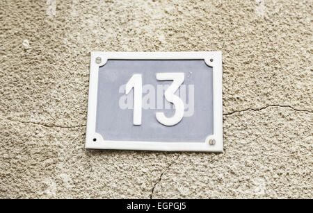 Number thirteen on a wall in a house, detail of a wall with a figure on a plate - Stock Photo