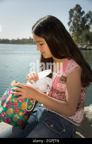 11 12 13 year old young person people Tween tweens Mexican heritage Hispanic-Caucasian child children opening birthday - Stock Photo