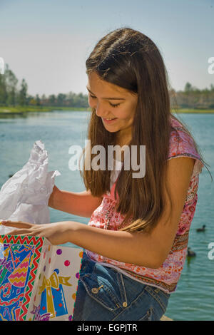 young person people Tween tweens Hispanic/Caucasian girl 11-13 year old child children opens opening  birthday present - Stock Photo