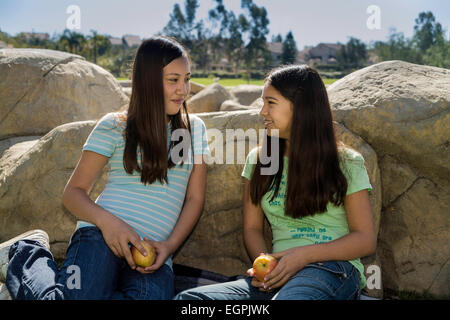 Two nature natural Tween tweens 11-12-13 year old olds Vietnamese-Caucasian Hispanic Mexican girls talking share - Stock Photo