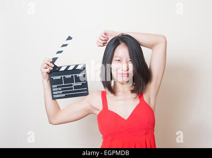 Young beautiful asian woman red dress make a funny face with clapperboard on white background - Stock Photo