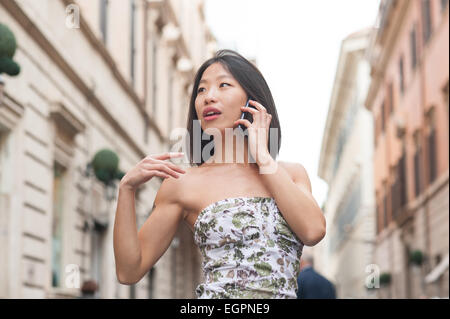 young beautiful asian woman looking around and talking using mobile egpne9 REPORT AFRIQUE International