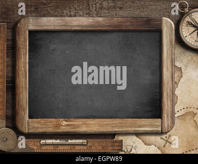 Treasure map, blackboard, old compass and ruler on wood desk. Adventure or discovery concept. - Stock Photo