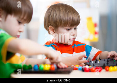 two kids brothers play together at table - Stock Photo