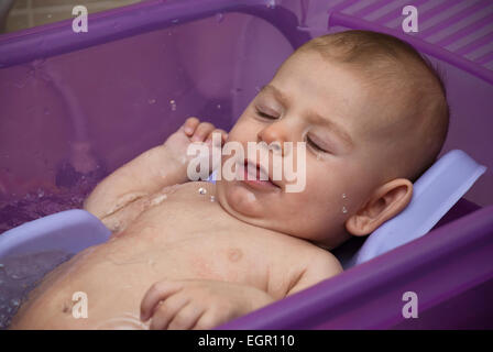 Happy smiling baby being bathed Model released - Stock Photo