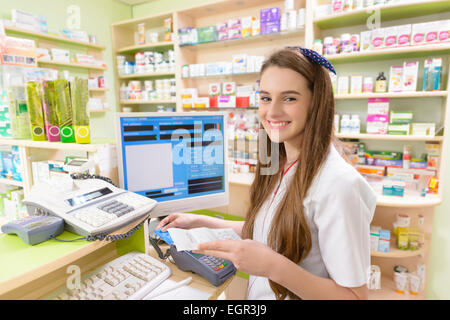 Young female pharmacist holding a receipt - Stock Photo
