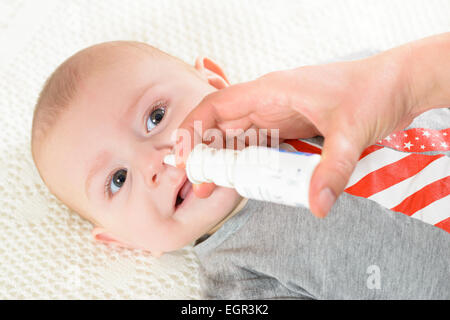 Woman using nasal spray for baby - Stock Photo