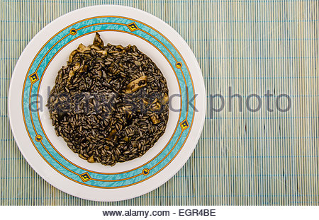 Arroz negro. Black rice. Typical spanish food in mediterranean zone made with rice, onion, tomato, squids and squid - Stock Photo
