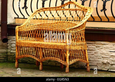 near the building costs wicker bench for rest - Stock Photo