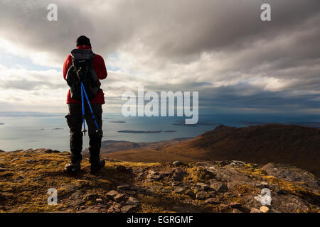 Hillwalker overlooking the sea from a hill in Coigach in the far north of Scotland - Stock Photo