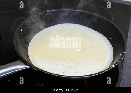 pancakes frying in the pan - Stock Photo