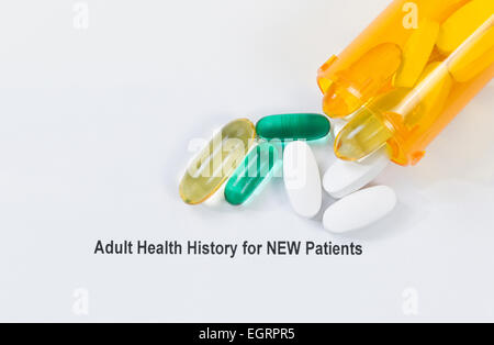 Close up overhead angled shot of pills spilling on to medical form with white background. - Stock Photo