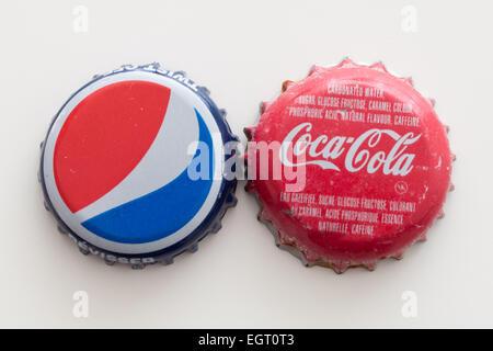 A Pepsi bottle cap and a Coca-Cola bottle cap. - Stock Photo