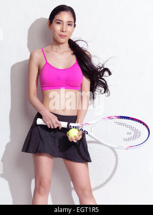 Portrait of a young Japanese woman with a tennis racket wearing a sporty outfit on white background - Stock Photo