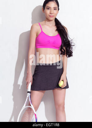 Portrait of a young Japanese woman with a tennis racquet wearing a sporty outfit on white background - Stock Photo