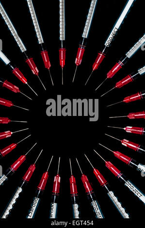 Used syringes arranged in a circle; concept shot for drug abuse - Stock Photo