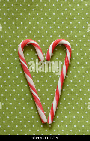 Red and white candy canes forming heart shape - Stock Photo