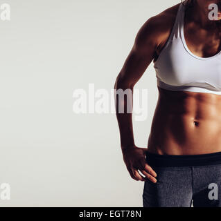 Close-up of woman with muscular body. Cropped image of fit young woman in sportswear on grey background with copyspace. - Stock Photo