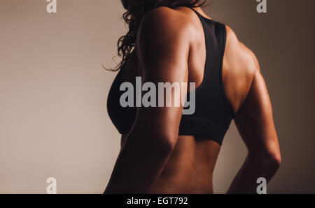Back of a fit and muscular woman athlete in sports bra. Rear view of fitness female with muscular body. Highlighted - Stock Photo