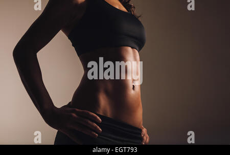 Close up of young woman's torso with copyspace. Perfect abdomen muscles of a female athlete on dark background with - Stock Photo