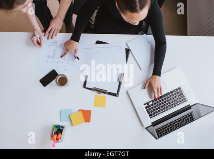 Business team working on a new plan with laptop. Top view of two young women executives working together with laptop - Stock Photo