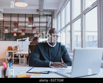 Portrait of confident young man sitting at his desk with laptop. African businessman working in modern office. - Stock Photo
