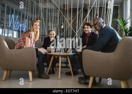 Portrait of multiethnic business team sitting in office lobby looking at camera smiling. Successful business team - Stock Photo
