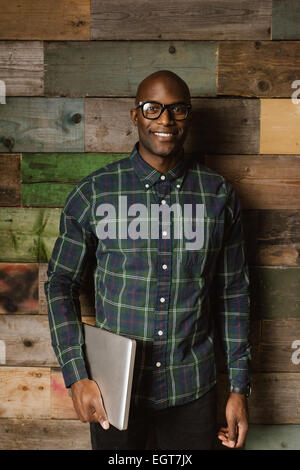 Portrait of young african student with laptop smiling at camera. Bald young man wearing glasses standing against - Stock Photo