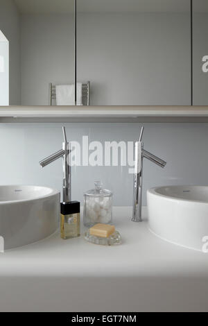 Symmetrical detail of twin hand basins with chrome mixer taps mounted on Corian vanity unit beneath mirrored cabinets - Stock Photo