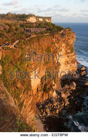 Tourists along the cliffs next to the Ulu Watu temple Pura Luhur. Bali. Uluwatu Temple is a Hindu temple set on - Stock Photo