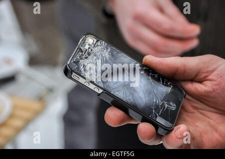 phone with a broken screen in a hand - Stock Photo
