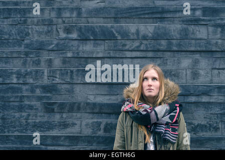Trendy young female student in warm winter fashion standing thinking or daydreaming leaning against a textured grey - Stock Photo