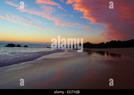 Pink and orange clouds reflected on Porthgwidden Beach at sunrise St Ives Cornwall England Europe - Stock Photo