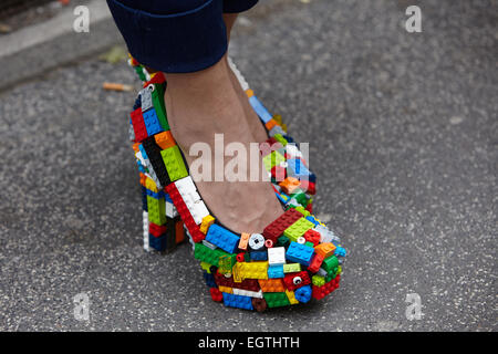 MILAN - FEBRUARY 26: Woman poses for photographers before Just Cavalli show in lego shoes Milan Fashion Week Day - Stock Photo