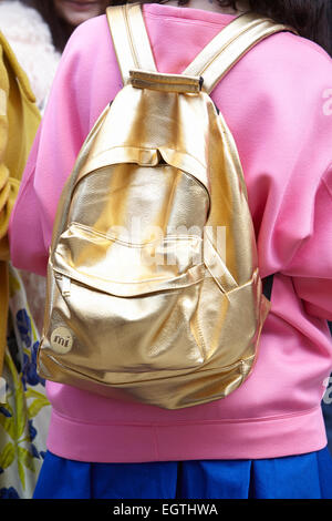 MILAN - FEBRUARY 26: Woman poses for photographers before Anteprima show with golden backpack Milan Fashion Week - Stock Photo