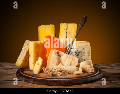 Various kind of cheese served on wooden table - Stock Photo